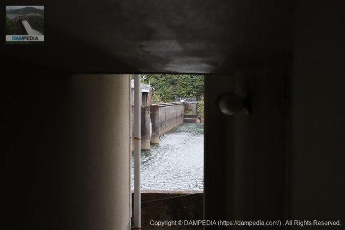 建物の隙間からダム湖側の堤体を望む
