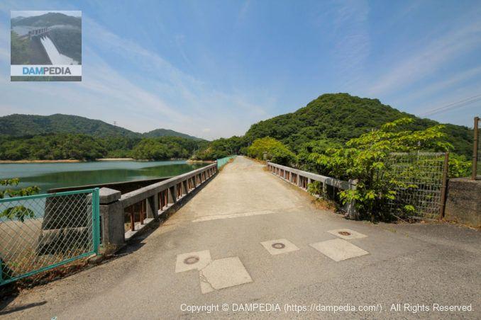 右岸より余水吐に架かる稲倉橋と天端を望む