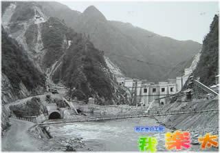 下流より堤体建設現場と仮排水トンネルを望む